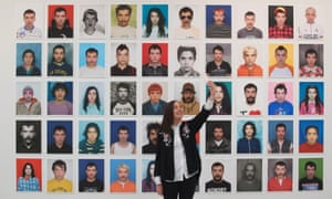 A visitor takes a selfie in front of a collection of daily passport photos by Juan Pablo Echeverri at the Selfie to Self-Expression exhibition at the Saatchi gallery