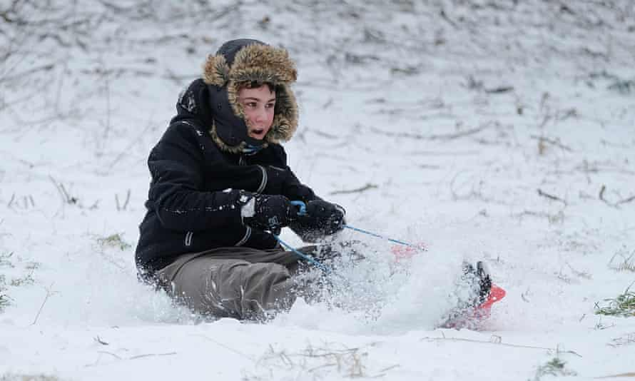 A boy goes sledging down a hill in the snow