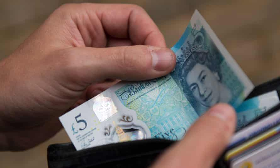 Person holding a wallet containing a £5 note
