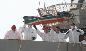 A body recovered by an Italian military ship from the Mediterranean is transferred to land at Reggio Calabria