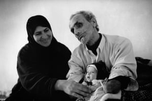 Abdulah, who lost both arms and his eyes when he tried to clear landmines from his farmland himself, is seen with his grandchild in 2007