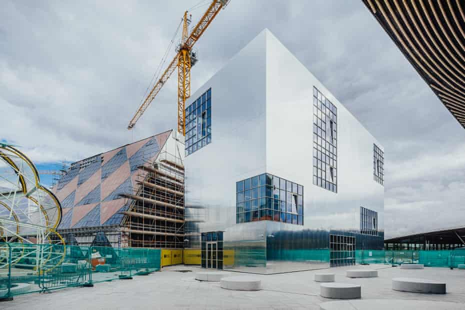 Mirror-polish … Barozzi Veiga's completed building, with 6a's chequerboard design alongside, and the 'caterpillar' food hall by SelgasCano taking shape left.