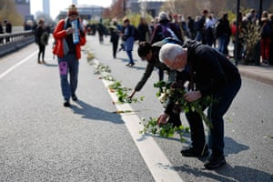 Protesters lay flowers on the road in the middle of Waterloo Bridge in London