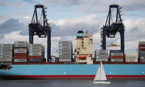 A container ship at Felixstowe with a yacht sailing by in the foreground