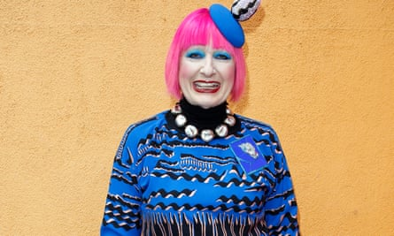 Zandra Rhodes with trademark pink hair and heavy make-up, in a bright blue dress with black markings