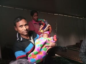 Alam Ansari and his wife, Seema, with their infant twin daughters outside the main hospital in New Delhi