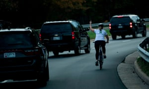 Juli Briskman gives the finger to President Donald Trump as he departs Trump National Golf Course in Sterling, Virginia.