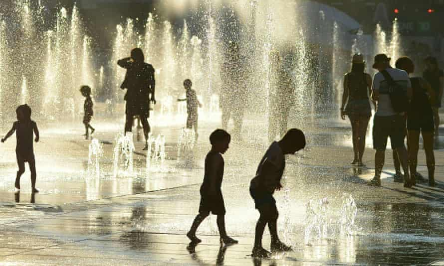 Children play in the water fountains at the Place des Arts in Montreal, Canada on 3 July 2018.