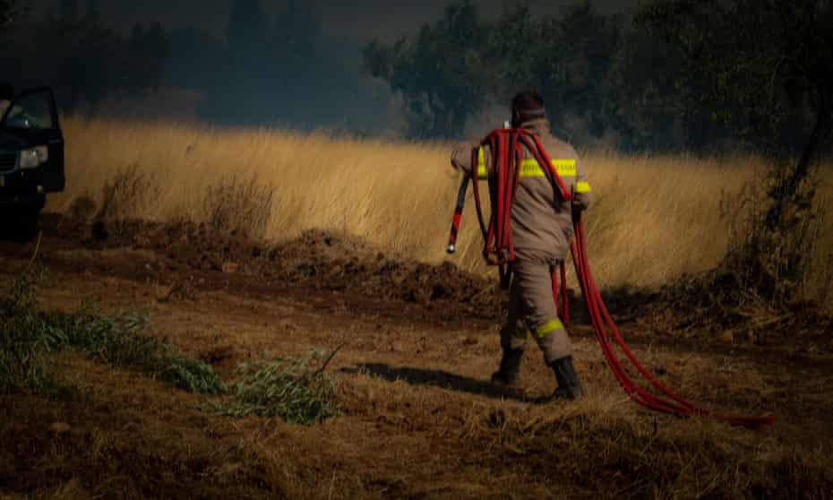 A firefighter battles wildfire near Athens in August.