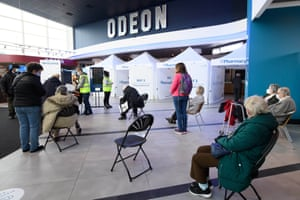 People wait to receive the Oxford/AstraZeneca vaccine at the opening of the first Pharmacy2U Covid-19 vaccination centre at the Odeon Cinema in Aylesbury on 21 January, 2021