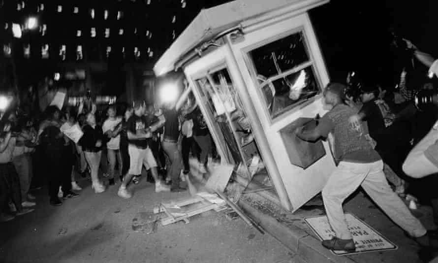 Rioters overturn a parking attendant booth at an LAPD center in downtown Los Angeles during the 1992 riots.