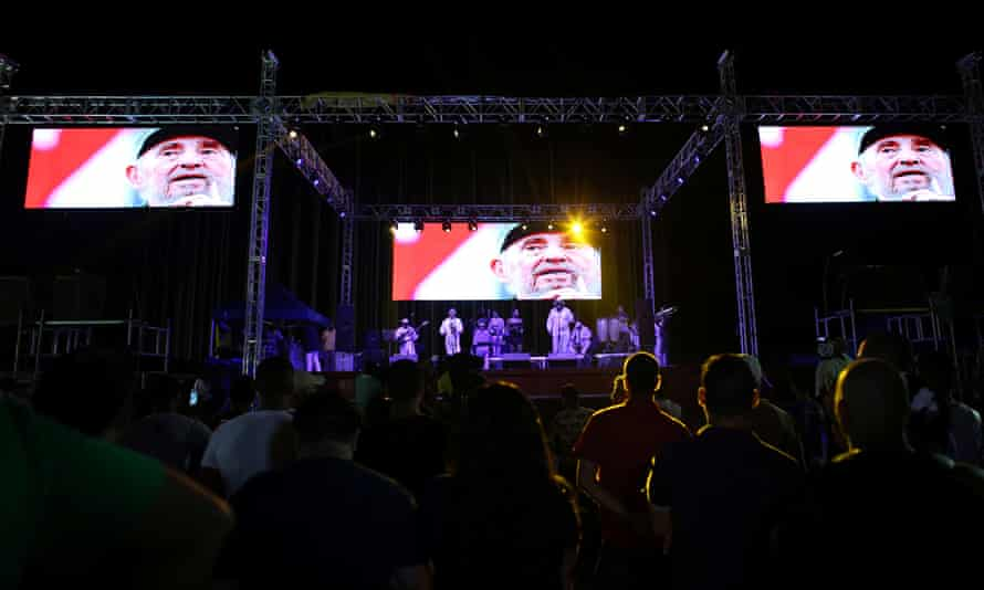 People look at pictures of Fidel Castro during a break in a concert celebrating his birthday