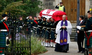 Soldiers carry the casket from the church following the funeral service