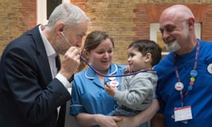 Labour leader Jeremy Corbyn pretends to use a stethoscope with 2-year-old Haroon, after he met NHS nurses, student nurses and midwives at Unison HQ.