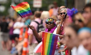 A woman waves a rainbow flag during a gay pride parade in Minneapolis. Estimates place the city's LGBTQ population at more than 10%.