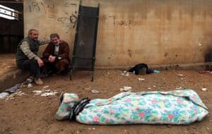 Mosul, Iraq: An Iraqi man mourns near the body of his son