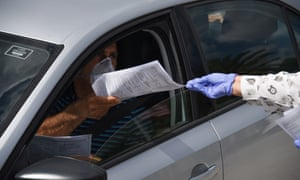 Employees in Miami, Florida, hand out unemployment applications to those seeking unemployment. More that 520,000 Floridians have applied for unemployment since 15 March, compared with 326,000 in all of last year.