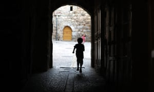 A child walks on an empty street in the old city of the West Bank town of Hebron, 31 May.