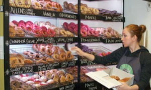 Member of staff at Holy Donut, Portland, Maine, puts doughnuts into a cardboard box from a display of the store's many doughtnuts.