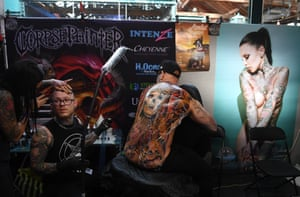 LondonA tattoo artist works on a man's back during the London Tattoo Convention at Tobacco Dock, in London