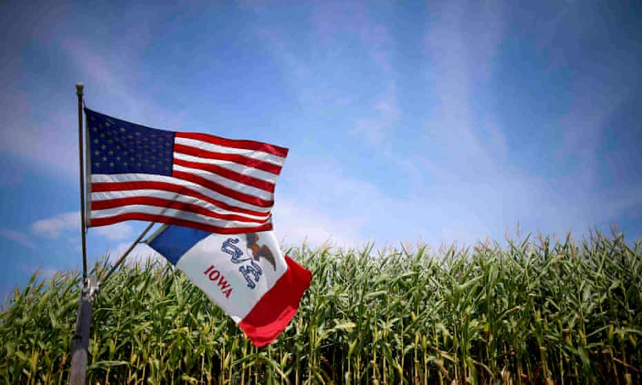 US and Iowa state flags fly next to a corn field in Grand Mound, Iowa.