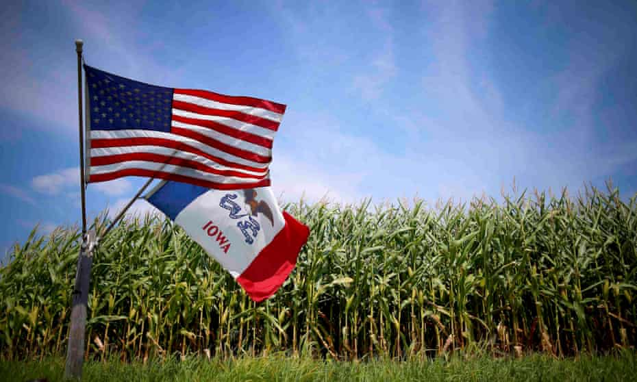 A US and Iowa state flags are seen next to a corn field in Grand Mound, Iowa, United States,