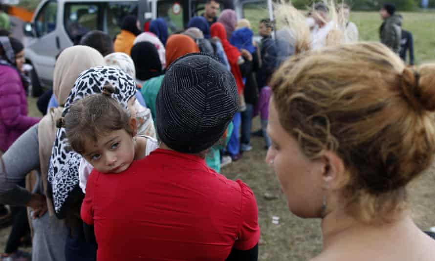People wait for food in a makeshift refugee camp near the Hungarian border in Serbia