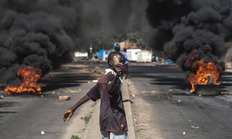 A protester throws rocks next to burning tyres during a demonstration against President Robert Mugabe.