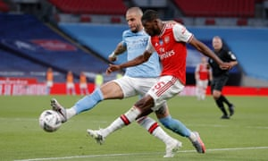 Arsenal's Ainsley Maitland-Niles puts a cross despite the efforts of Kyle Walker of Manchester City.