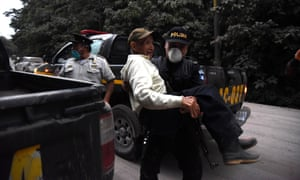 A policeman carries an elderly evacuee in Alotenango, 55 km southwest of Guatemala City