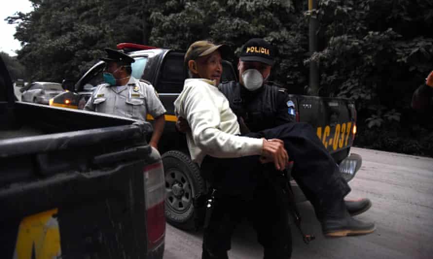 A policeman carries an elderly evacuee in Alotenango, 55 km southwest of Guatemala City