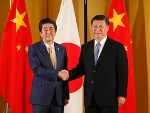 Chinese President Xi Jinping (right) and Japanese Prime Minister Shinzo Abe (left) shake hands at the start of their talks at a Osaka hotel today.