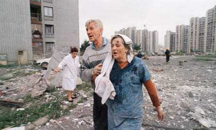A wounded woman is helped to get out of her apartment building after it was hit by a rocket fired from Bosnia Serb positions, June 1995.