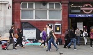 Pedestrians walk past a homeless man sleeping next to a London tube station.