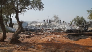 People walk on rubble at the site of a US raid in Barisha, Syria