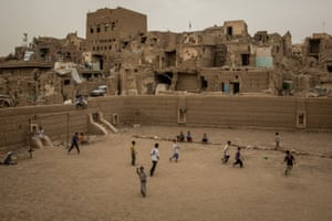 Children play football in front of ruined buildings of Sa'ada al-Gadim, a historic heritage site