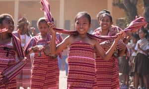 Students in traditional dress welcome Australian delegates to Mauraba school in Timor-Leste, where a satellite dish has connected the school with Australia's Northern Territory. .