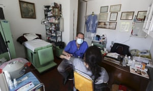 Dr. Rafael Galindo, a general practitioner and surgeon, examines a patient in his office in the Iztapalapa neighborhood of Mexico City. Iztapalapa, the capital's largest borough, is one of the hardest hit by the new coronavirus pandemic.