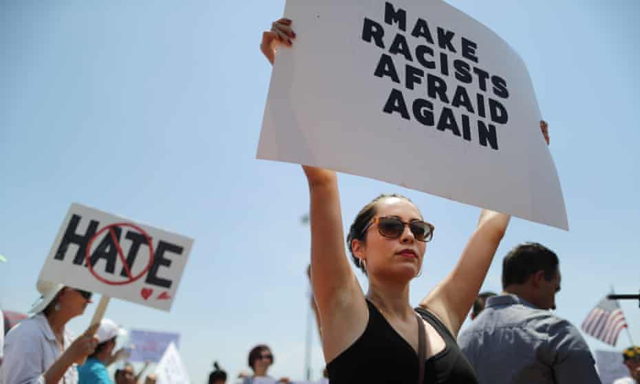 A demonstrator holds a sign at a protest against Donald Trump's visit to El Paso, Texas, on 7 August.