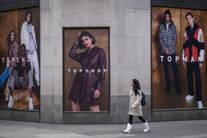 A Londoner walks past posters at the rear of the Topshop clothing retailer.