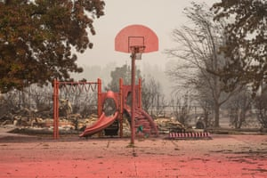 A basketball hoop in Talent tinged red by the fire retardant