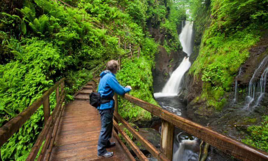 Walking beneath Ess-na-Larach waterfall, County Antrim.