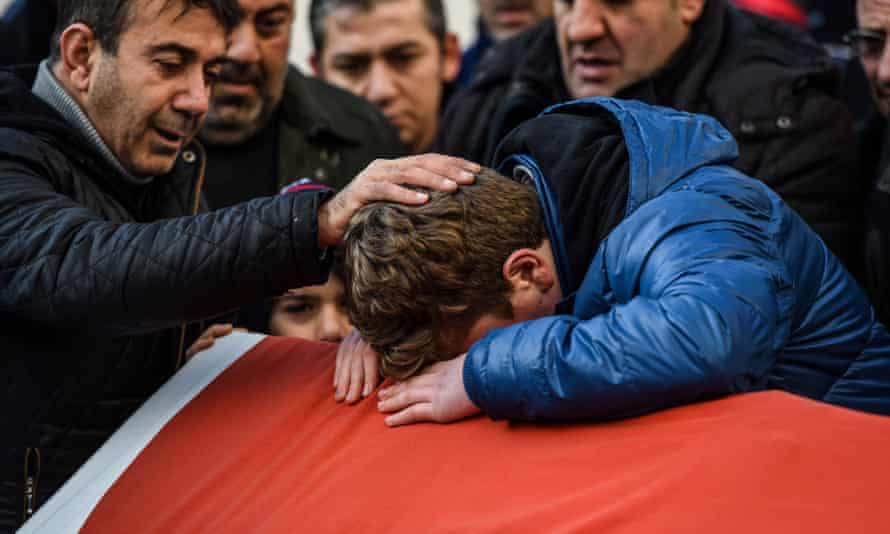 Relatives of Ayhan Arik, one of the victims of the Reina nightclub attack, mourn during his funeral