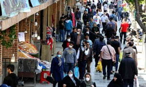 Iranians, some wearing protective gear amid the Covid-19 pandemic, shop on a street by the Grand Bazaar market in Tehran, on 18 April.