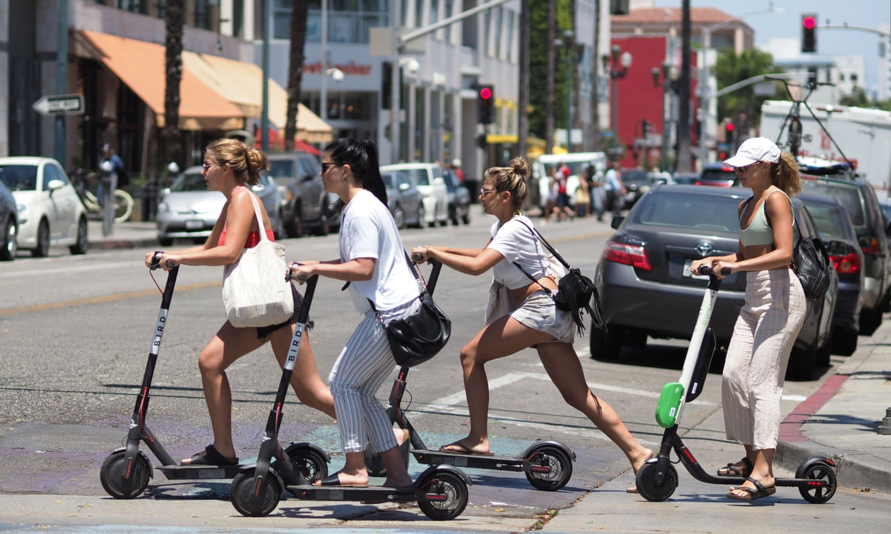 People ride e-scooters in Santa Monica, California.