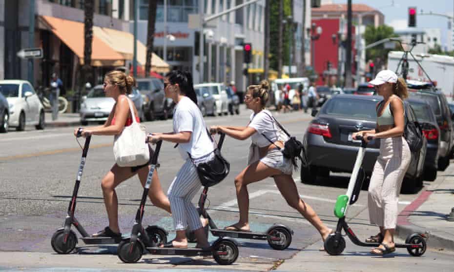 People ride e-scooters in Santa Monica, California.