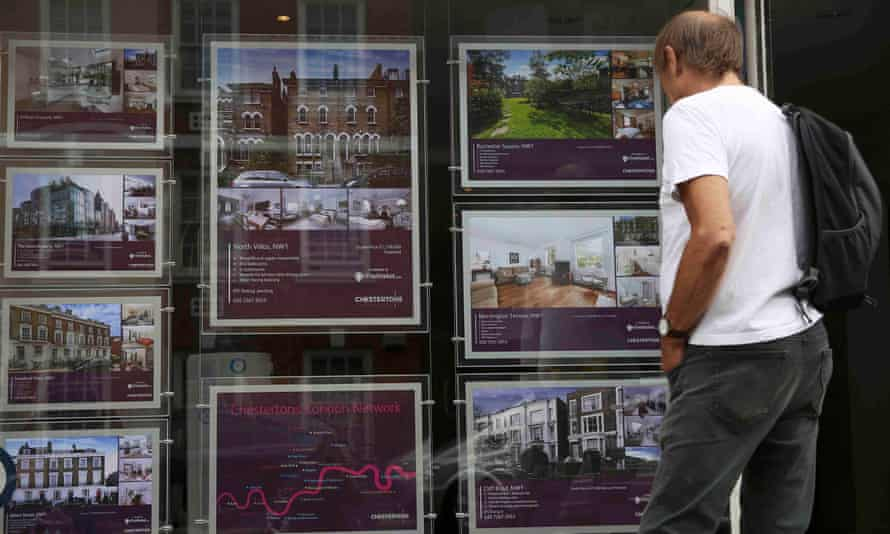 A man looks at property for sale at an estate agents in London