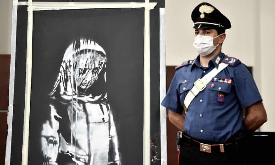 A member of Italy's carabinieri stands alongside the recovered mural