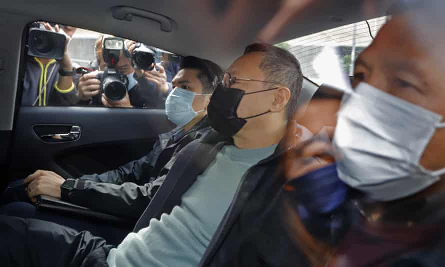 The legal scholar Benny Tai (C), is driven away in a car after he was among those arrested