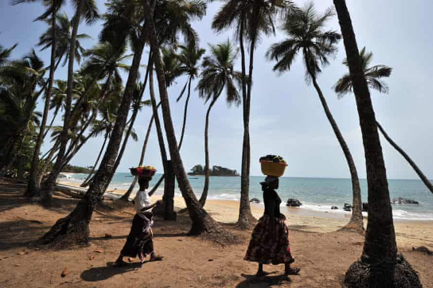 two women carry baskets on their heads by a palm tree-fringed beach